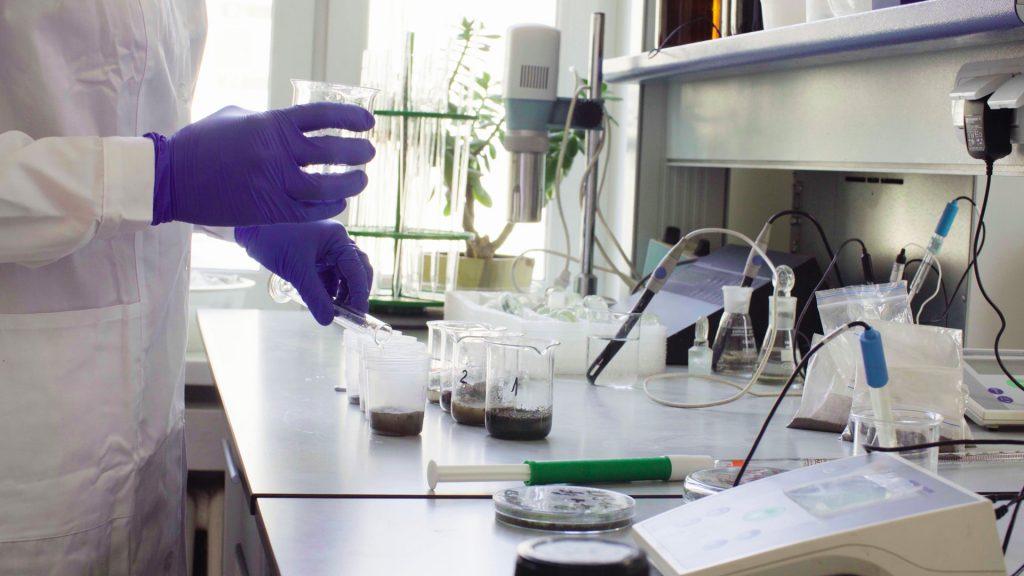 pessoa no laboratório com amostras de solo fazendo testes